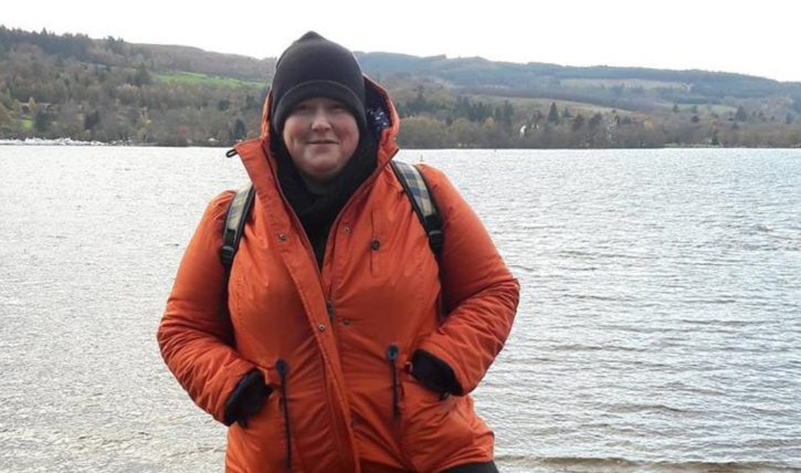 A woman standing in front of a lake, wearing a beanie and thick jacket